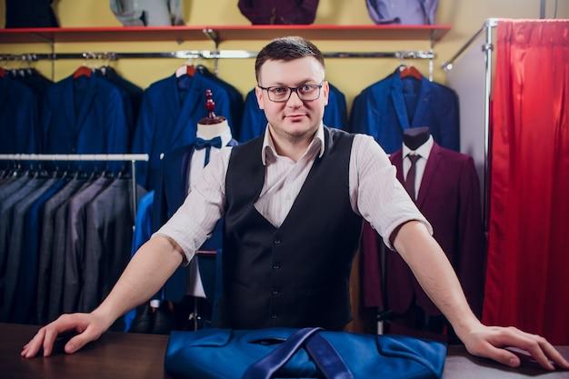 El hombre está comprando traje en la tienda