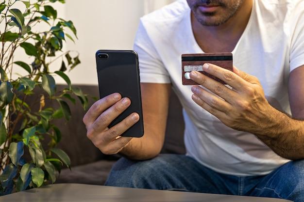 Hombre de compras en línea pagando el pedido en línea con el teléfono y la tarjeta de crédito desde casa