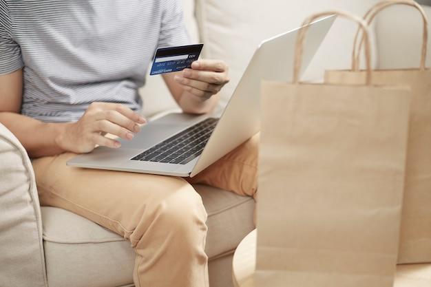 Hombre de compras en línea usando la computadora portátil y la tarjeta de crédito trasera billetera electrónica