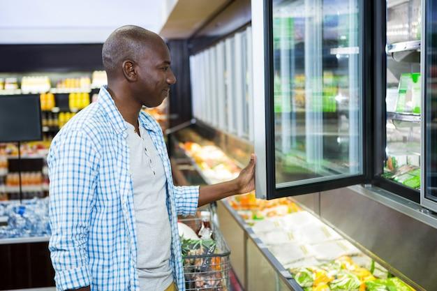 Hombre de compras en la sección de comestibles