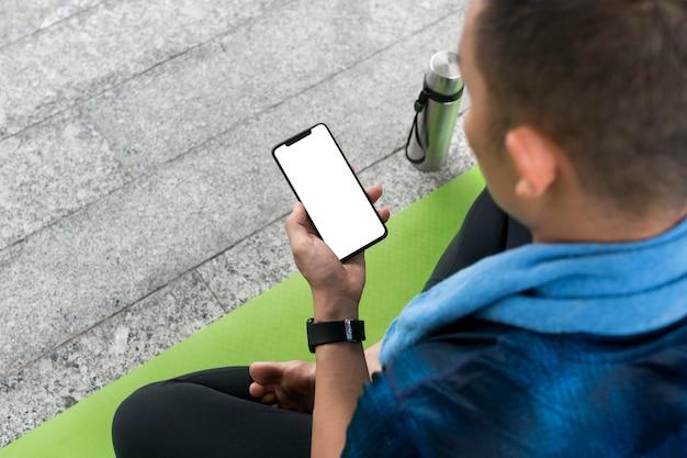 Hombre comprobando el teléfono inteligente antes de hacer algo de yoga