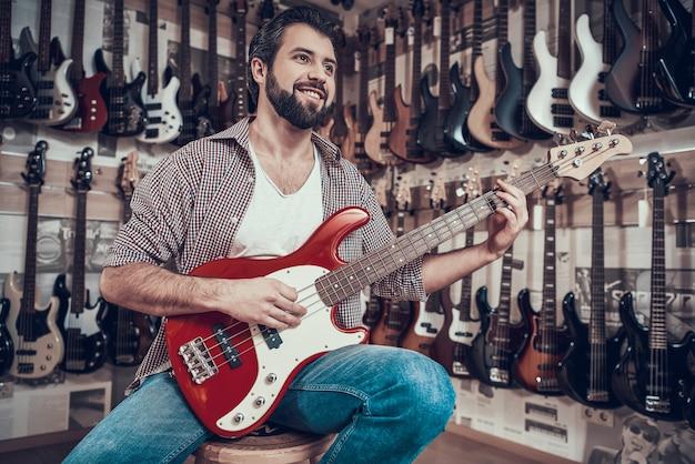 El hombre comprueba la guitarra eléctrica en la tienda de instrumentos musicales.