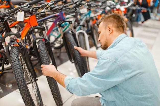 El hombre comprueba el neumático de la bicicleta, compras en la tienda de deportes