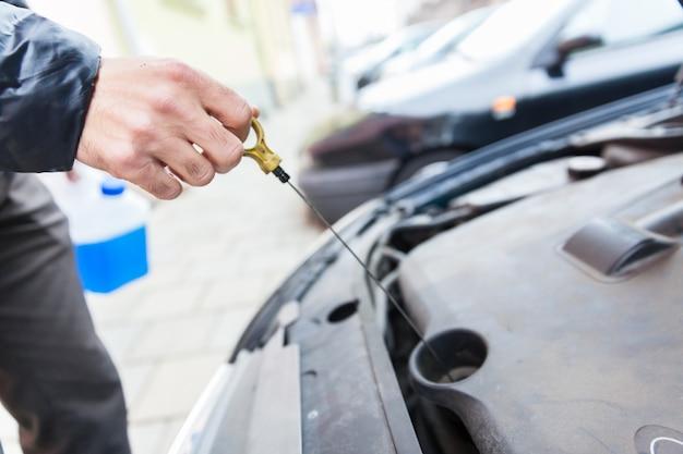 El hombre comprueba el nivel de aceite en el motor del automóvil.