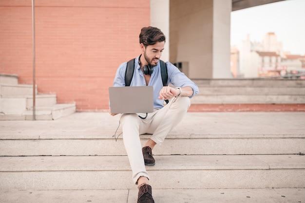 Hombre con la computadora portátil mirando la hora de reloj