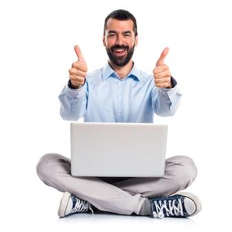 Hombre con la computadora portátil con el pulgar para arriba