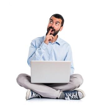 Hombre con la computadora portátil que hace gesto de la sorpresa