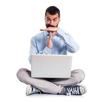 Hombre con la computadora portátil que hace tiempo hacia fuera gesto