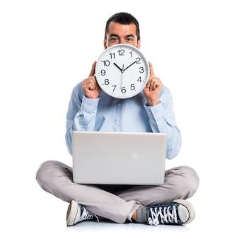 Hombre con la computadora portátil que sostiene un reloj