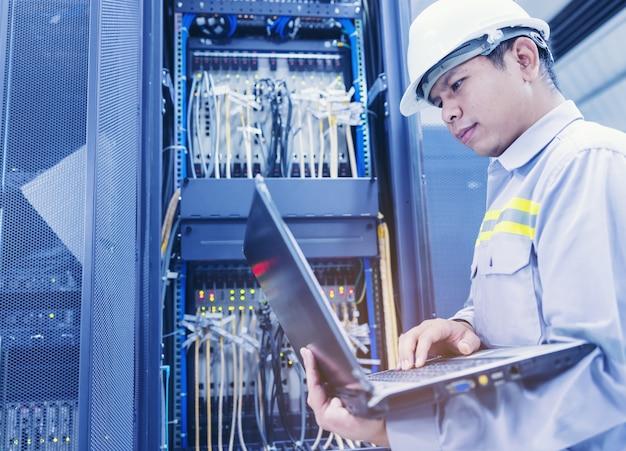 Un hombre con una computadora portátil se sienta en la sala de servidores del centro de datos. el administrador del sistema trabaja cerca de los racks con los servidores.