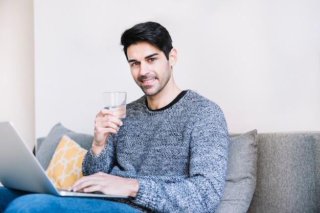 Hombre con computadora portátil y vidrio
