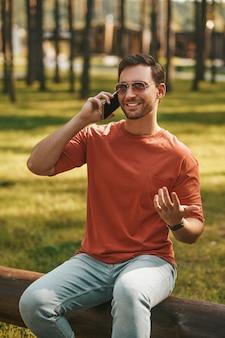 Hombre comunicándose por teléfono inteligente en la naturaleza