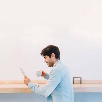 Hombre con café usando tableta