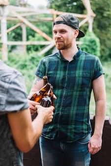 Hombre con gorra chocando las botellas de cerveza marrón con su amigo