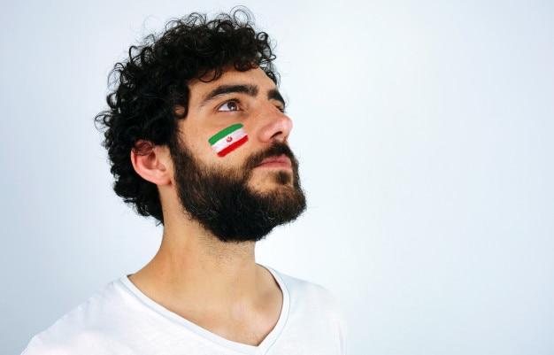 Hombre con la bandera de irán maquillaje en la cara. aficionado al deporte escuchando el himno de su cuenta