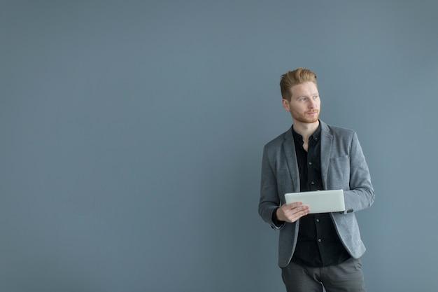Hombre con tableta junto a la pared
