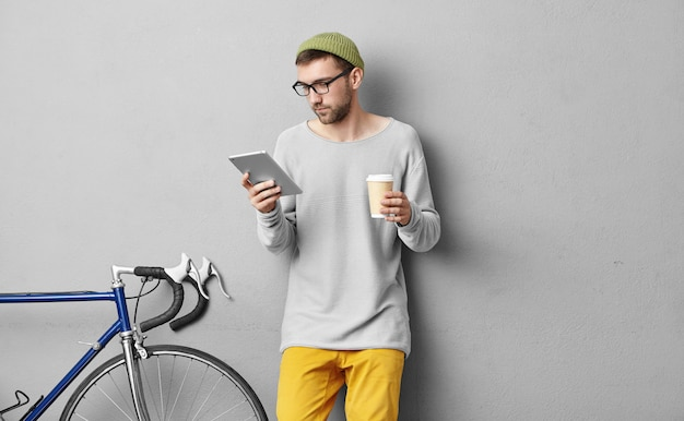 Hombre concentrado en gafas grandes de moda, con tableta en una mano y café para llevar en la otra, va a ir en bicicleta a las montañas, lee en internet qué cosas mejor llevar