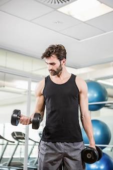 Hombre concentrado levantando pesas en el estudio