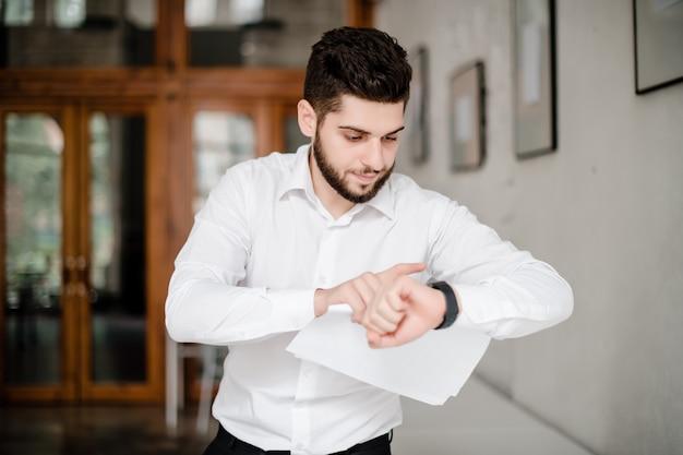 Hombre concentrado mirando su reloj comprobando el tiempo