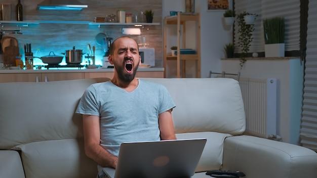 Hombre concentrado, navegar por la información en la red usando una computadora portátil