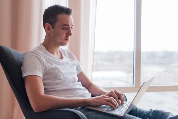Hombre concentrado que se sienta en chaor y que mecanografía en el ordenador portátil cerca de ventana
