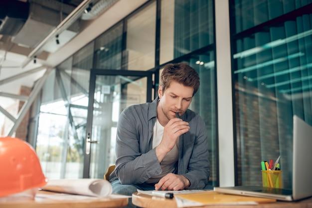 Hombre concentrado reflexionando sobre el plan de construcción en interiores