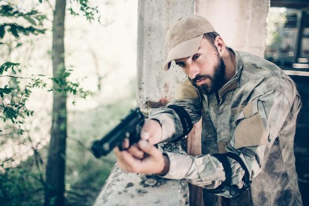El hombre concentrado y valiente está de pie cerca de la salida y con el arma en sus manos. el hombre está sosteniendo el dedo en el gatillo. hireling es tranquilo. el esta esperando.