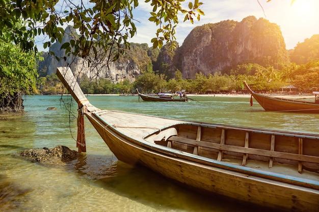 Un hombre conduce un bote de cola larga, un taxi marítimo lleva a los turistas en un día soleado cerca de la playa tropical