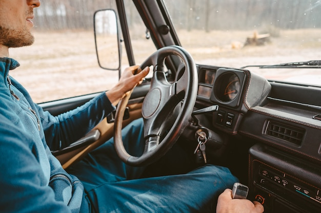 Hombre conduciendo suv coche por camino forestal
