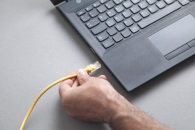 El hombre conecta el cable de red a la computadora portátil.