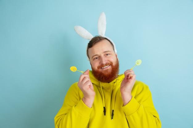 Hombre de conejito de pascua con emociones brillantes sobre fondo azul de estudio