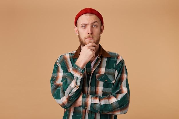 Un hombre confiado con barba vestido con una gorra roja fresca y una camisa a cuadros tiene su mano en la barbilla