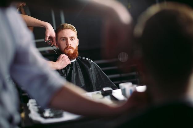 Hombre confiado que visita al estilista en peluquería de caballeros.