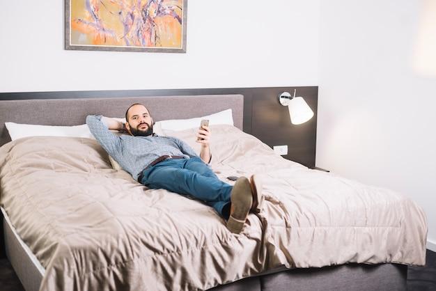 Hombre confiado relajante en la cama