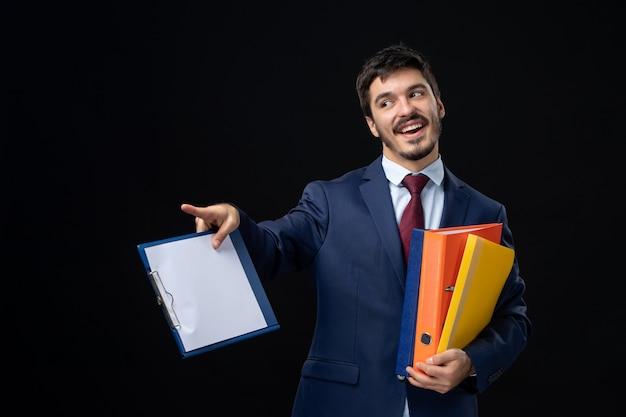 Hombre confiado en traje sosteniendo varios documentos y apuntando hacia adelante en la pared oscura aislada