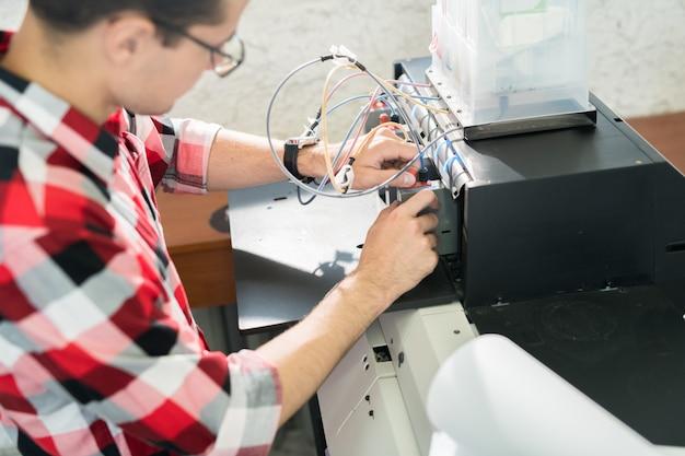 Hombre configurando equipos de impresión