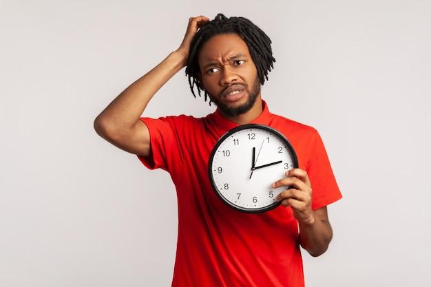 Hombre confundido frotándose la cabeza sosteniendo en las manos un gran reloj de pared, no tiene tiempo, preocupado por la fecha límite