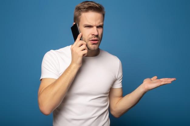 Hombre confundido hablando por teléfono inteligente y gesticulando aislado en azul