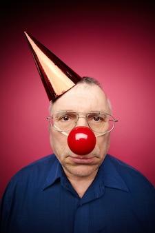 Hombre confundido con nariz roja de payaso y gorro de cumpleaños