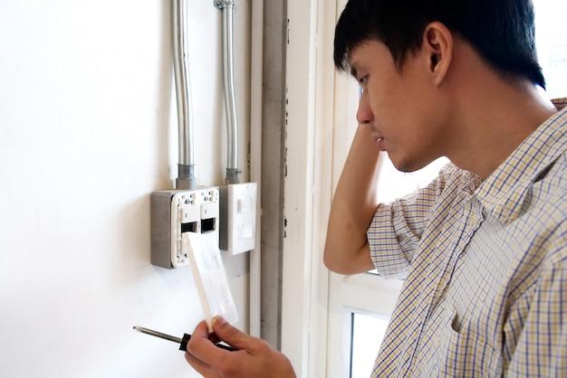 Un hombre confuso para arreglar el interruptor eléctrico en la pared.