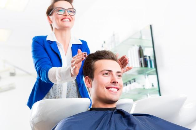 Hombre del consejo del peluquero en corte de pelo en barbería