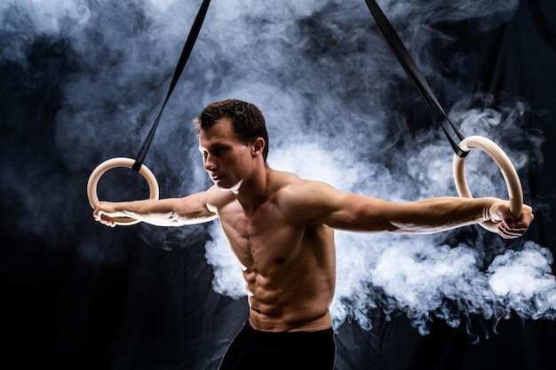 Hombre de construcción muscular haciendo calistenia en anillos de gimnasia interior sobre fondo negro ahumado