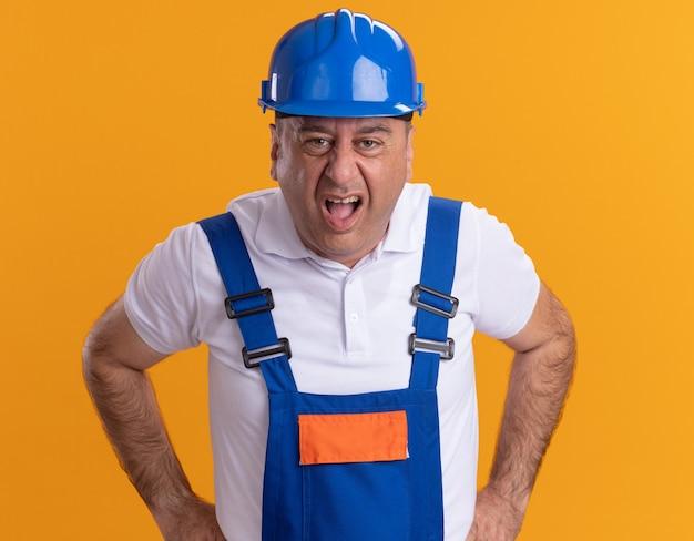 Hombre constructor adulto molesto en uniforme mira al frente aislado en la pared naranja