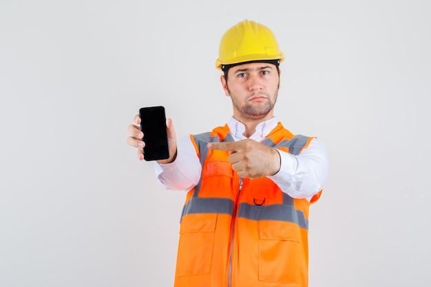 Hombre constructor apuntando con el dedo al teléfono inteligente en camisa, uniforme y mirando serio, vista frontal.
