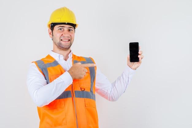 Hombre constructor apuntando con el dedo en el teléfono inteligente en camisa, uniforme y mirando alegre, vista frontal.