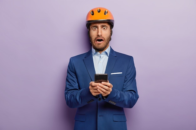 Hombre constructor asustado viste traje formal y casco