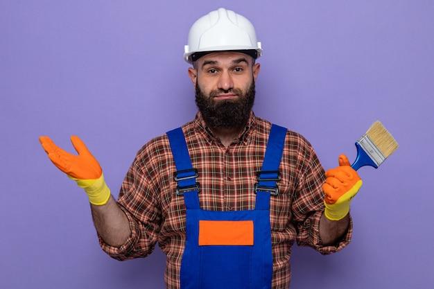 Hombre constructor barbudo en uniforme de construcción y casco de seguridad con guantes de goma sosteniendo pincel mirando a cámara confundido extendiendo los brazos hacia los lados sobre fondo púrpura