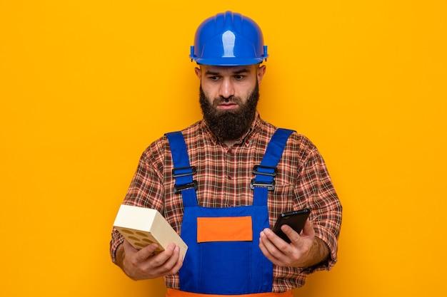 Hombre constructor barbudo en uniforme de construcción y casco de seguridad con ladrillo y teléfono móvil que parece confundido teniendo dudas sobre fondo naranja