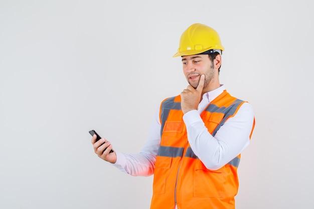 Hombre constructor en camisa, uniforme pensando mientras mira el teléfono inteligente y se ve positivo, vista frontal.