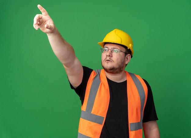 Hombre constructor en chaleco de construcción y casco de seguridad mirando hacia arriba con cara seria apuntando con el dedo índice a algo de pie sobre fondo verde